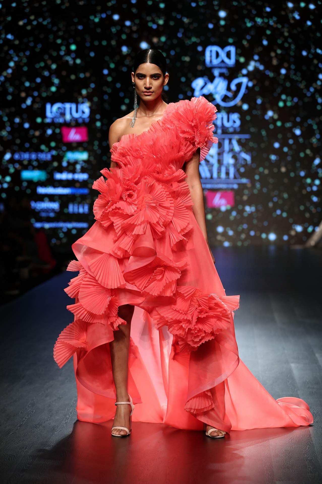 ca0ccbc979 Frill and froth. Pleated frills and ruffles were a prominent feature of  Dolly J's collection. Red carpet-ready gowns with asymmetrical hems were  paired with ...