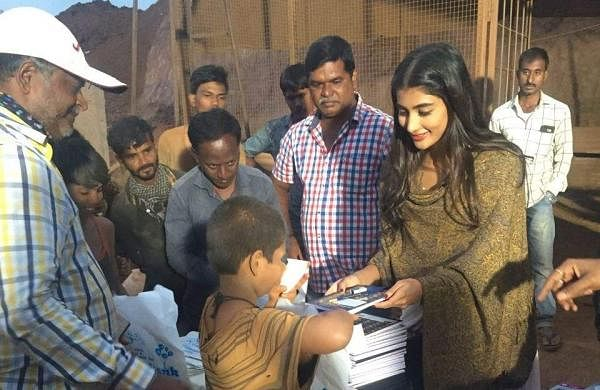Pooja Hegde distributes books on the sets