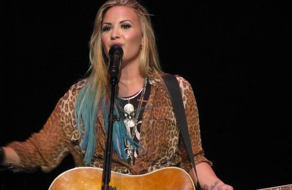 Demi_Lovato_playing_the_guitar_smile