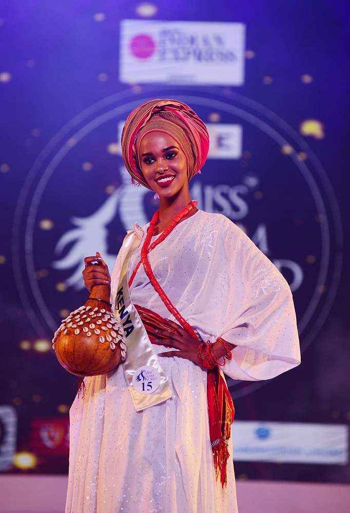 Kenya's Fahima Abdi walks the ramp with traditional red head gear and a white gown at Indulge Miss Glam World 2018.