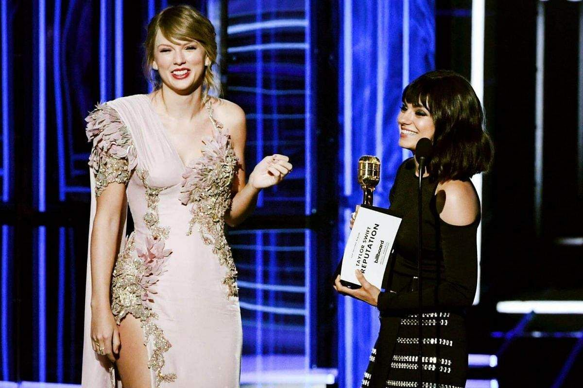 Taylor Swift (left) accepts the Top Selling Album award for Reputation from Mila Kunis onstage during the 2018 Billboard Music Award.