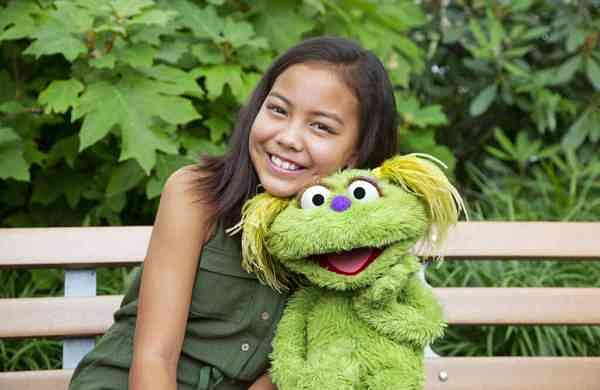 Salia Woodbury with Karli (Flynn Larsen/Sesame Workshop via AP)