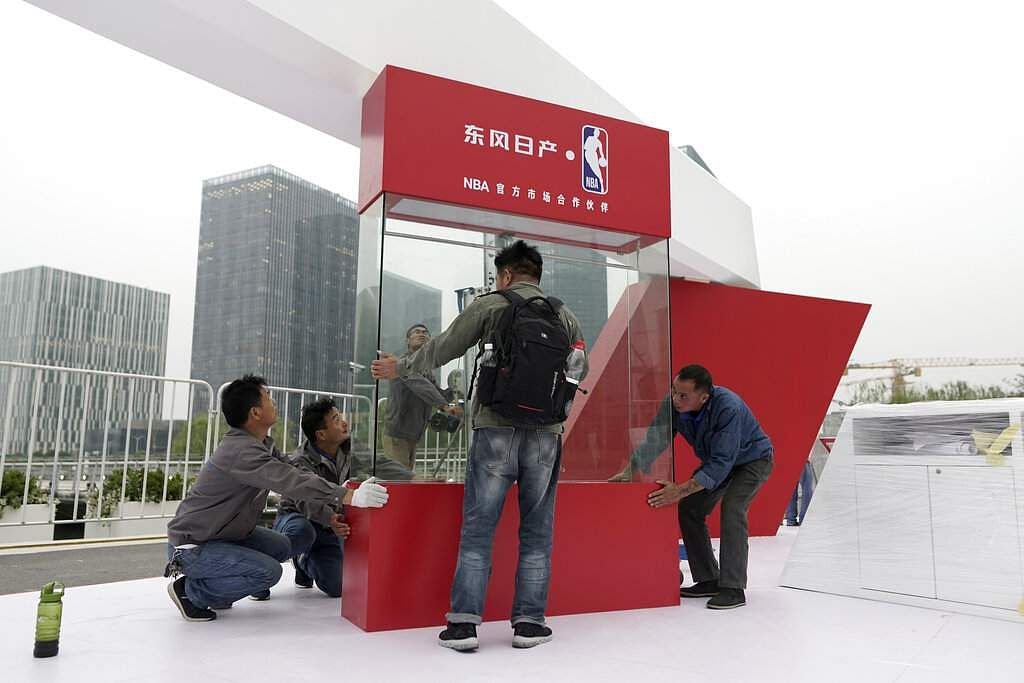 Workers dismantle signage for an NBA fan event in Shanghai, China (AP Photo)