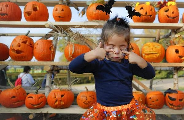 A little girl presses her eyelids after placing the pumpkin she carved on a shelf at The Halloween Pumpkin Fest in Bucharest, Romania. (AP Photo/Vadim Ghirda)