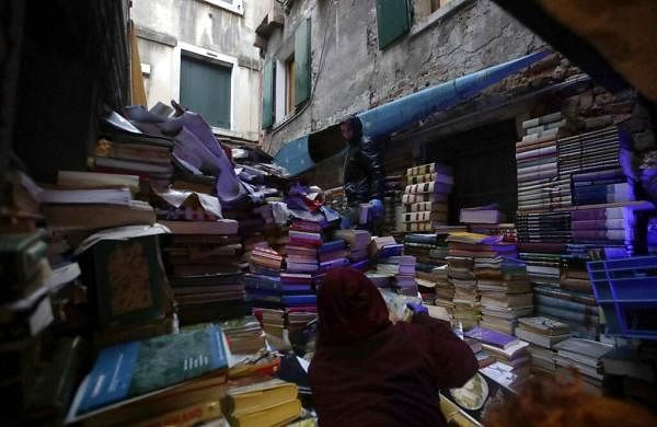 Volunteers pile up damaged books from renowned bookstore 'Acqua Alta' (High Water) after flooding in Venice, Italy  (AP Photo/Luca Bruno)