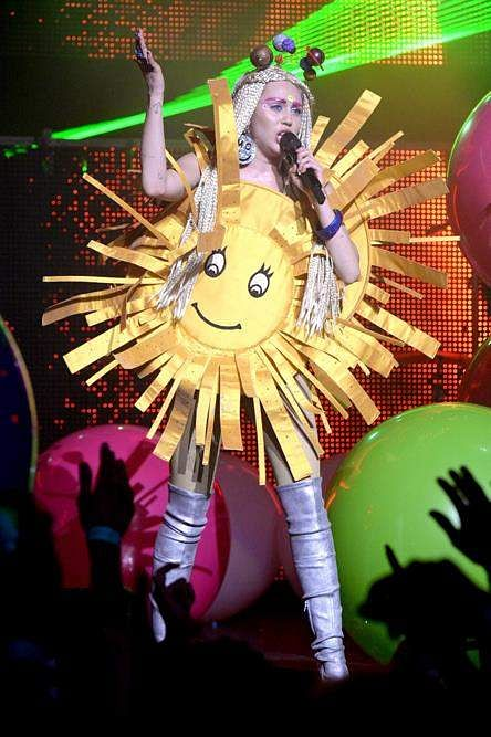 A bright Miley Cyrus in a sun costume, glitter boots, and a planetary headband