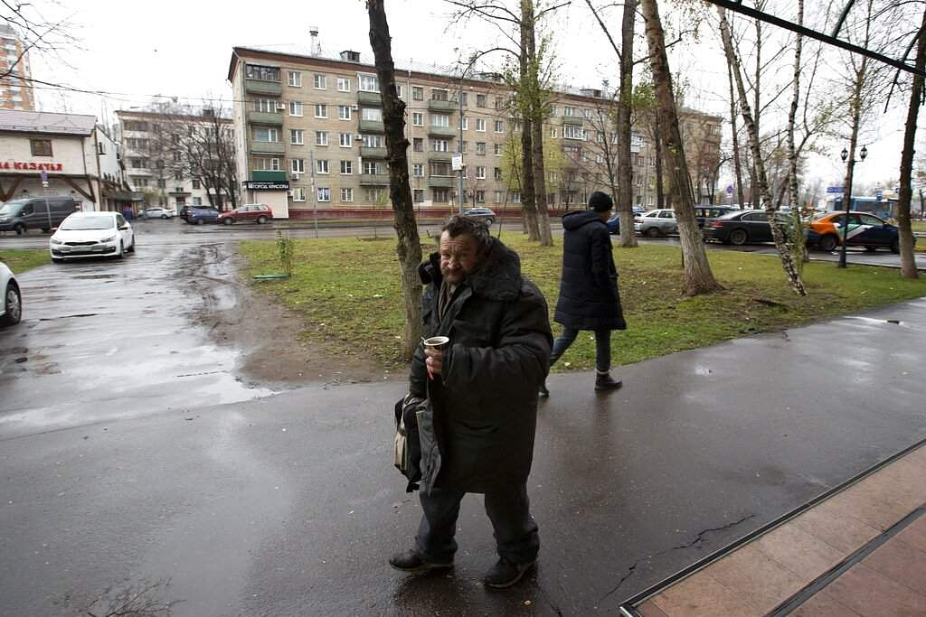 A homeless man walks on a street in Liublino, a working class suburb in Moscow. The city's suburbs are the focus of a new exhibition in the Russian capital. (AP Photo/Alexander Zemlianichenko)