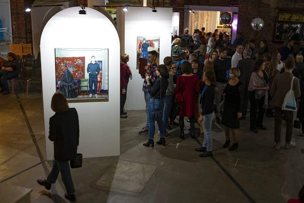 Visitors look at works showing an extreme outsider's view of Moscow reality by self-taught painter Pasmur Rachuiko, in the Gogol Center in Moscow, Russia. (AP Photo/Alexander Zemlianichenko)