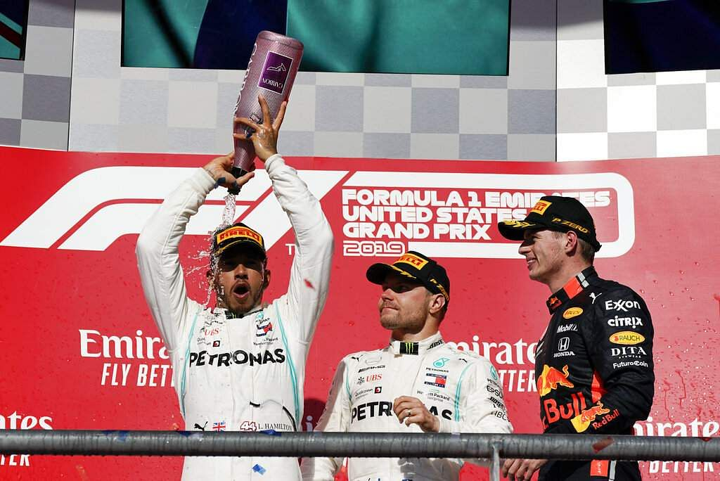 Lewis Hamilton celebrates as Valtteri Bottas and Max Verstappen watch following the Formula One U.S. Grand Prix auto race at the Circuit of the Americas in Austin, Texas. (AP Photo/Chuck Burton)