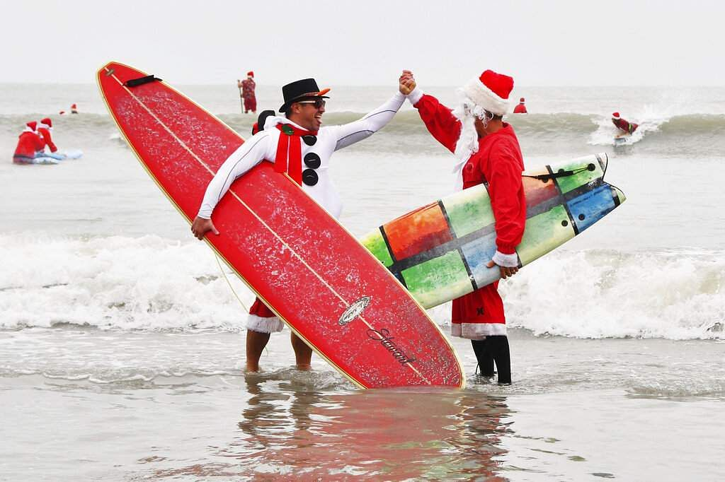 Surfing Santas (Malcolm Denemark/Florida Today via AP)