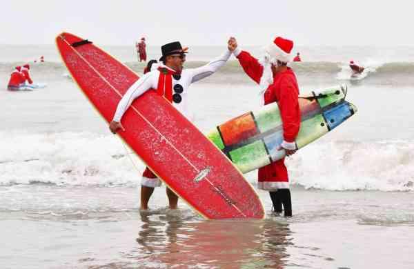 Surfing Santas (Malcolm Denemark/Florida Today via AP)