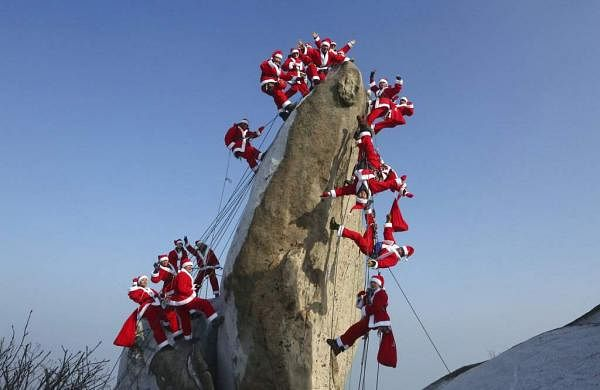 Mountain climbers in Santa Claus outfits pose during an event to hope for safe climbing and to promote Christmas charity on the Buckhan mountain in Seoul, South Korea. (AP Photo/Ahn Young-joon)