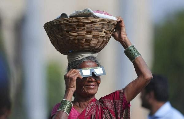 A roadside vendor holds a special filter and watches a partial solar eclipse in Hyderabad, India. (AP Photo/Mahesh Kumar A)