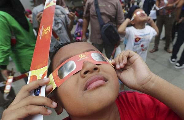 A child looks up at the sun wearing protective glasses to watch a solar eclipse from Jakarta, Indonesia. (AP Photo/Tatan Syuflana)