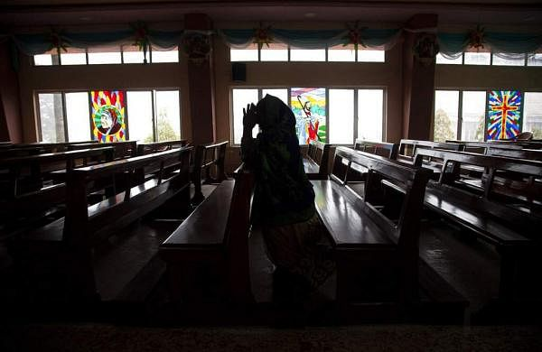 An Indian Christian woman offers prayers at a church on Christmas in Gauhati. Christmas is a national holiday celebrated with much fanfare in India. (AP Photo/Anupam Nath)