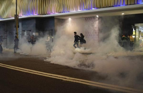 Residents react to teargas as police and protesters confront each other on Christmas Eve in Hong Kong. (AP Photo/Kin Cheung)