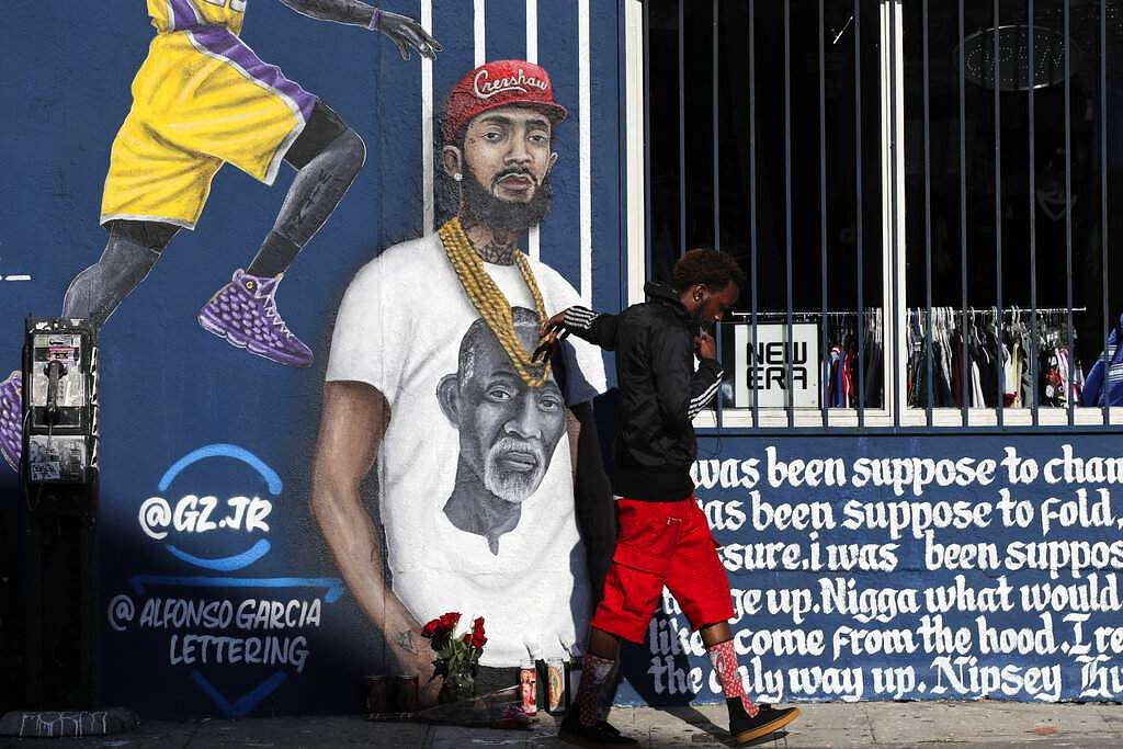 A man touches a mural depicting slain rapper Nipsey Hussle in Los Angeles. Hussle was shot and killed Sunday, March 31, outside of his clothing store in Los Angeles. (AP Photo/Jae C. Hong)