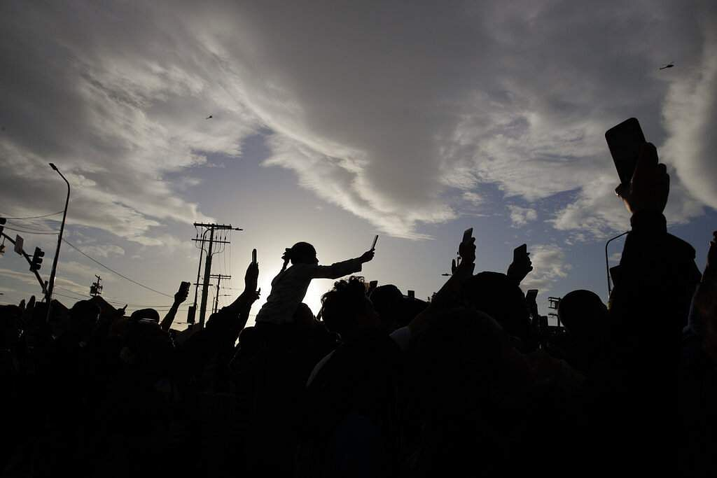 People hold up their smartphones to record the hearse carrying the casket of slain rapper Nipsey Hussle. (AP Photo/Jae C. Hong)