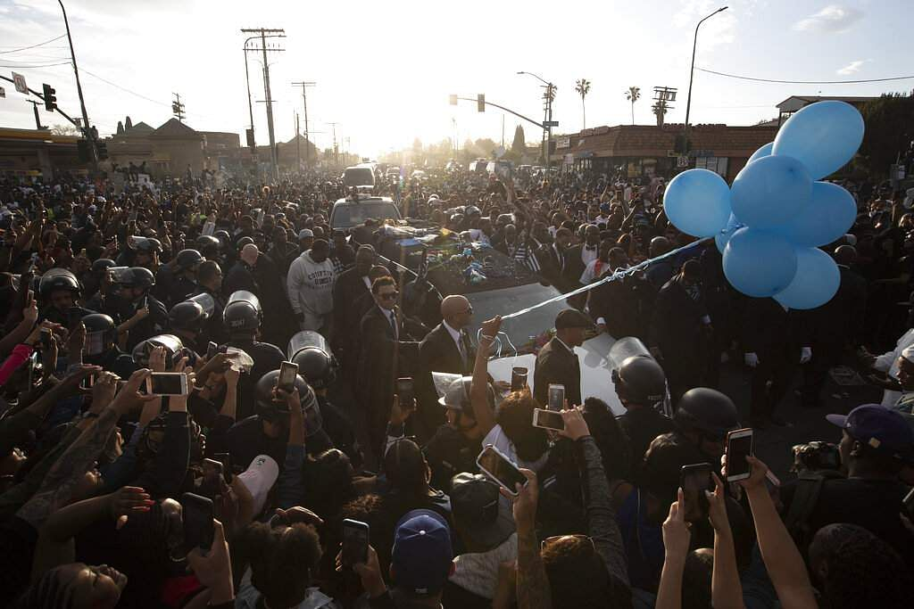 A hearse carrying the casket of slain rapper Nipsey Hussle passes through a large crowd on its 25-mile trek through the streets of South Los Angeles. (AP Photo/Jae C. Hong)
