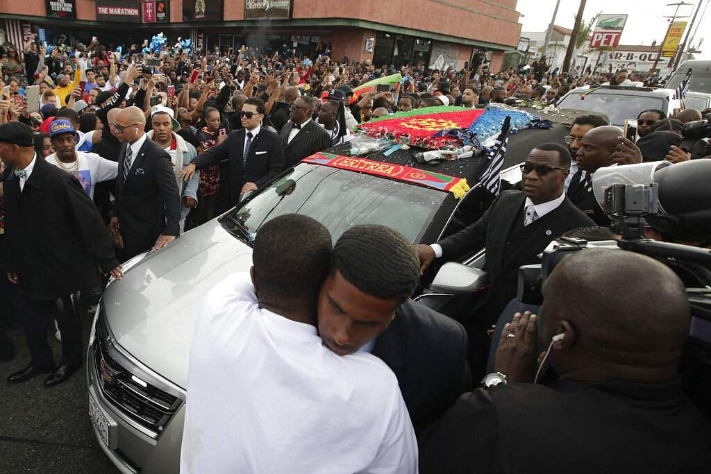 Two men hug as a hearse carrying the casket of slain rapper Nipsey Hussle passes through the crowd. The 25-mile procession traveled through the streets of South Los Angeles. (AP Photo/Jae C. Hong)