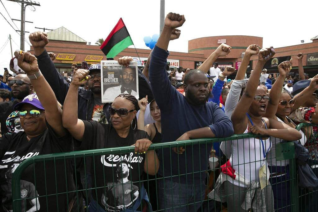 People hold up their fists waiting for a hearse carrying the casket of slain rapper Nipsey Hussle. The 25-mile procession traveled through the streets of South Los Angeles. (AP Photo/Jae C. Hong)