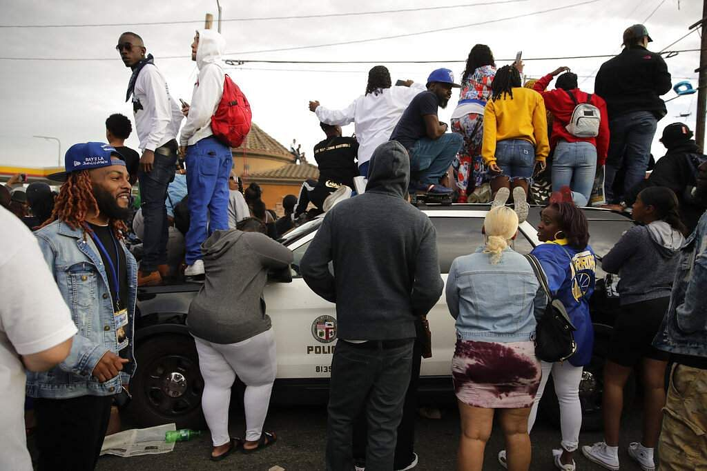 People climb on a police vehicle to watch a hearse carrying the casket of slain rapper Nipsey Hussle. The 25-mile procession traveled through the streets of South Los Angeles. (AP Photo/Jae C. Hong)