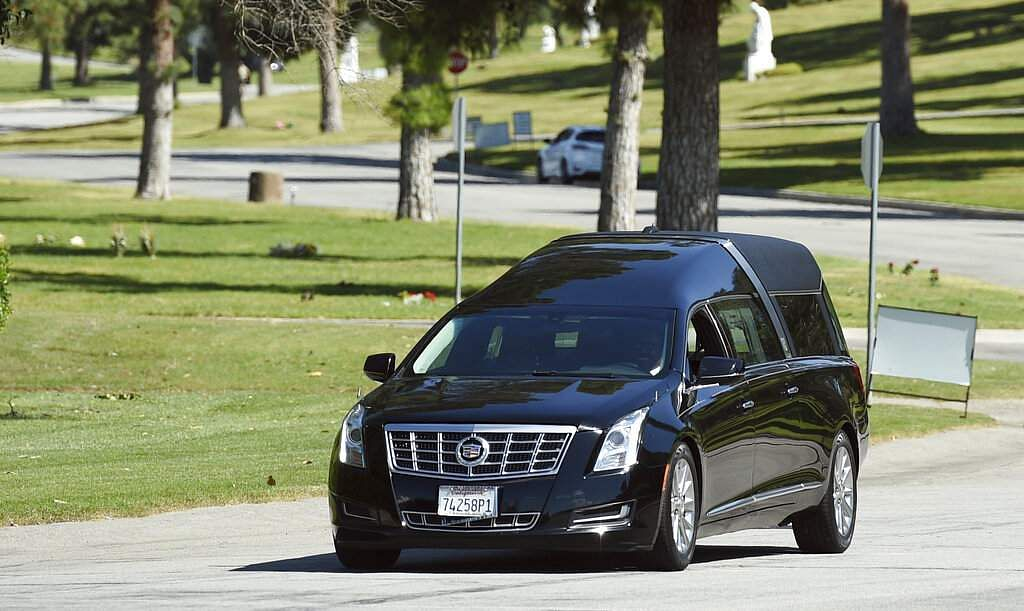 A hearse leaves a burial service for the late rapper Nipsey Hussle at Forest Lawn Hollywood Hills cemetery, Friday, April 12, 2019, in Los Angeles. (Photo by Chris Pizzello/Invision/AP)
