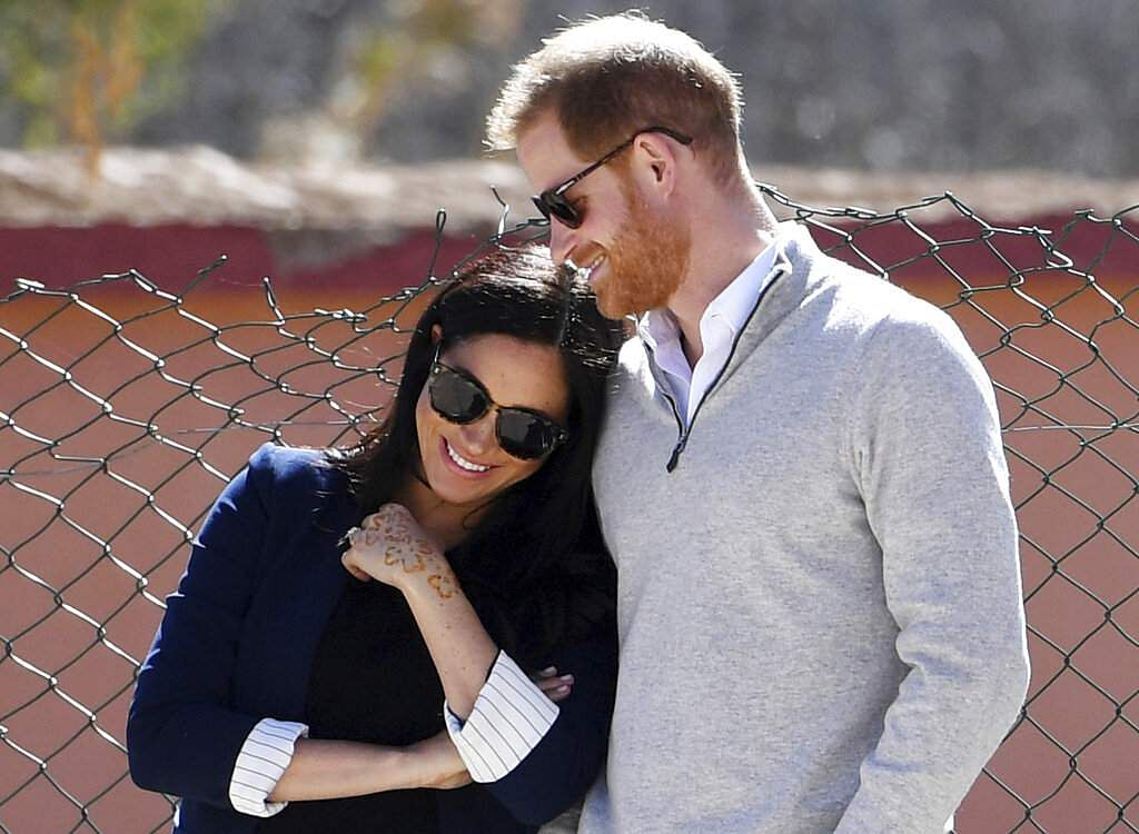 Prince Harry and Meghan watch children playing football at a school in the town of Asni, in the Atlas mountains, Morocco on Feb 24, 2019. (Facundo Arrizabalaga/Pool via AP)