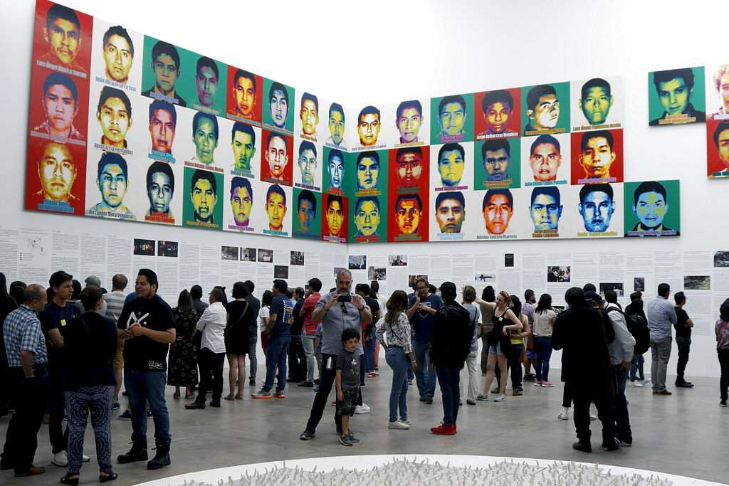 People stand under the portraits of 43 college students who went missing in 2014 in an apparent massacre, by Chinese concept artist and government critic Ai Weiwei. (AP Photo/Claudio Cruz)