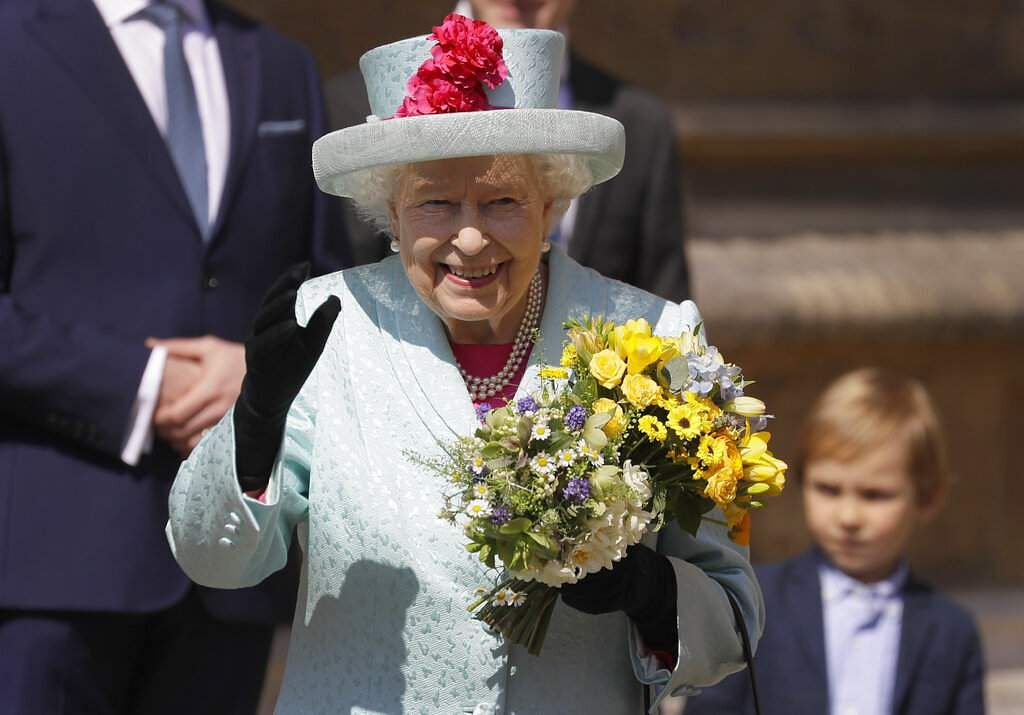 Britain's Queen Elizabeth II waves to the public as she leaves after attending the Easter Mattins Service at St. George's Chapel, at Windsor Castle in England. (AP Photo/Kirsty Wigglesworth)