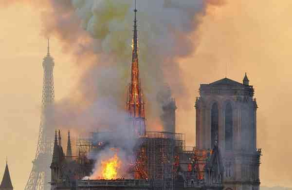 File photo: With the Eiffel Tower behind, flames and smoke rise from the blaze at Notre Dame Cathedral in Paris (AP Photo/Thierry Mallet)