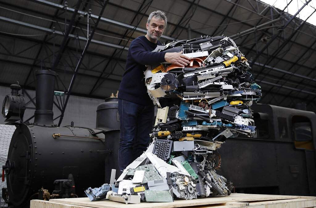 Designer Piet Hein Eek with his creation, Electronic Man, of recycled plastic from various electronic devices, at the RO Master's Pieces exhibition, in Milan, Italy. (AP Photo/Luca Bruno)
