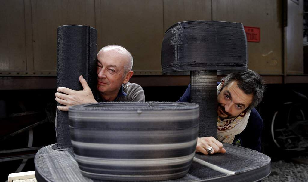 Designers Piero and Francesco Lissoni with their creation set consisting of a bowl, a vase and a lamp, made of upcycled plastic, at the RO Plastic - Master's Pieces exhibition. (AP Photo/Luca Bruno)