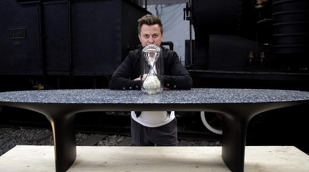 Australian designer Brodie Neill with his creation Capsule: Ocean Plastic Hourglass, on a table made of his self-created Ocean Terrazzo material, of plastic waste from oceans. (AP Photo/Luca Bruno)
