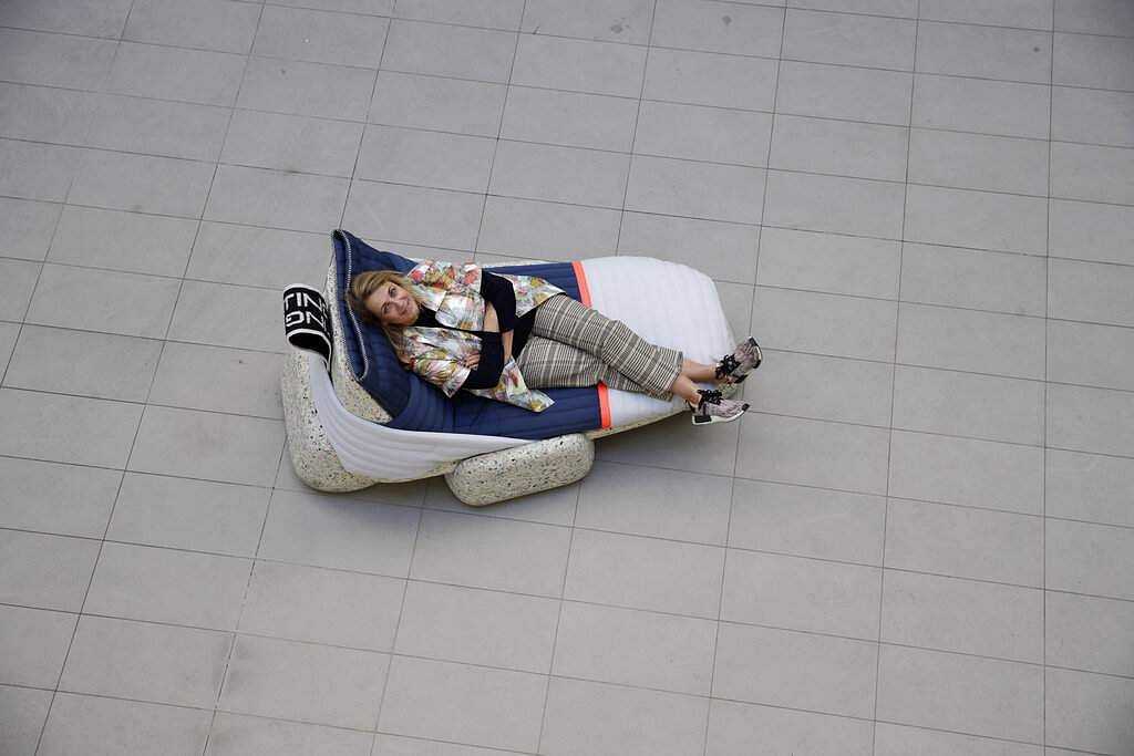 Designer Patricia Urquiola sits on her creation, Wasting Time Daybed, of upcycled plastic for the RO Plastic - Master's Pieces show, on the sidelines of Milan's Furniture Fair. (AP Photo/Luca Bruno)