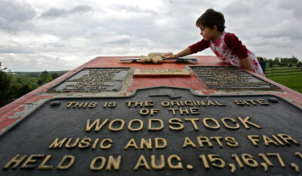 Emma Cenholt, 3, of Trumbull, Conn, playing on a memorial at the site of the Woodstock Music and Arts Fair in Bethel, NY. Woodstock 50 is less than a few months away. (AP Photo/Mike Groll)