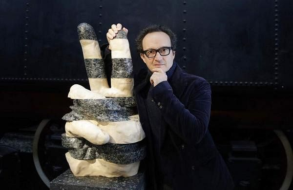 Designer Lucio Micheletti with his creation, Victory, made with maple wood and recycled plastic from bottles and containers, at the RO Plastic - Master's Pieces exhibition. (AP Photo/Luca Bruno)