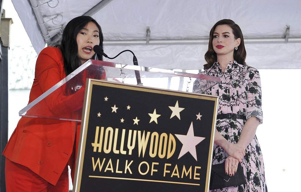 Actress Awkwafina speaks as Anne Hathaway looks on during a ceremony honouring the actress with a star on the Hollywood Walk of Fame, in Los Angeles. (Photo by Richard Shotwell/Invision/AP)