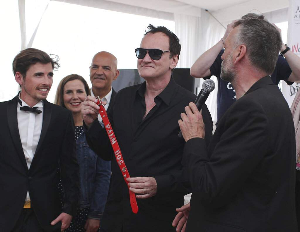 Director Quentin Tarantino poses with the Palm Dog collar award for the the dog Brandy that appeared in his film 'Once Upon a Time in Hollywood' at Cannes. (AP Photo/Petros Giannakouris)