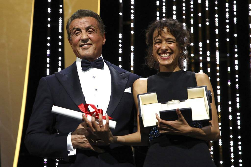 Director Mati Diop holds the grand prix Palme d'Or award for the film 'Atlantique' presented by actor Sylvester Stallone during the awards ceremony at Cannes. (Photo by Vianney Le Caer/Invision/AP)