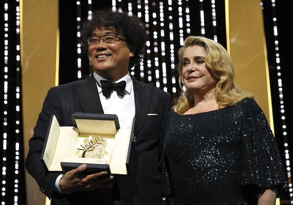 Director Bong Joon-ho, winner of the Palme d'Or award for the film 'Parasite' and actress Catherine Deneuve during the awards ceremony at Cannes. (Photo by Vianney Le Caer/Invision/AP)