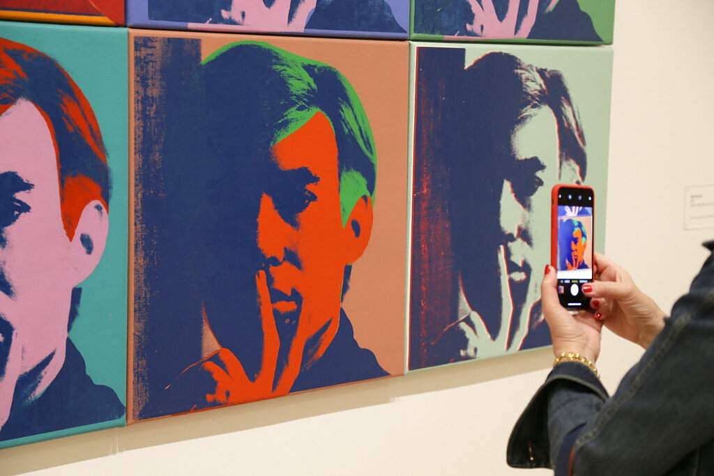 A woman records one of a series of self-portraits at the exhibition, 'Andy Warhol _ From A to B and Back Again', in San Francisco. (AP Photo/Eric Risberg)