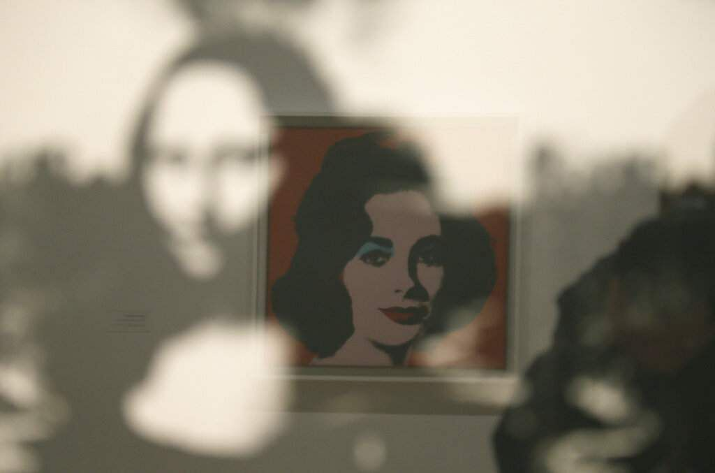 A display of female icons, Elizabeth Taylor is reflected in an image of the Mona Lisa at the exhibition, 'Andy Warhol _ From A to B and Back Again' in San Francisco. (AP Photo/Eric Risberg)