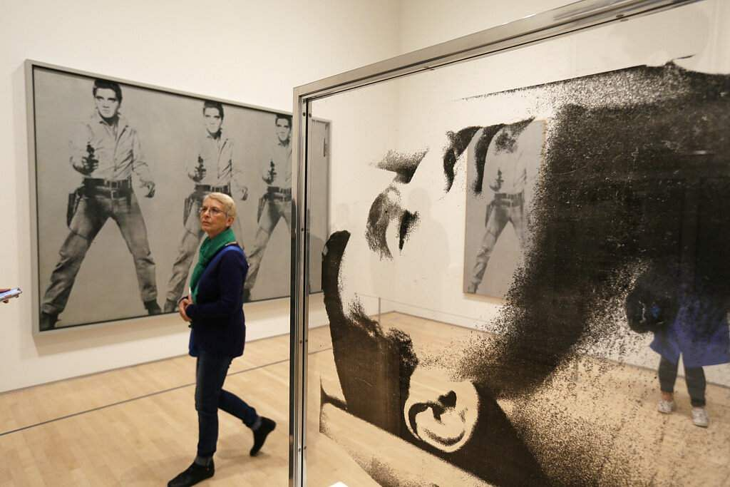 A woman walks past 'Large Sleep,' a silkscreen ink on plexiglass and the 1963 piece 'Triple Elvis' at the exhibition, 'Andy Warhol _ From A to B and Back Again'. (AP Photo/Eric Risberg)