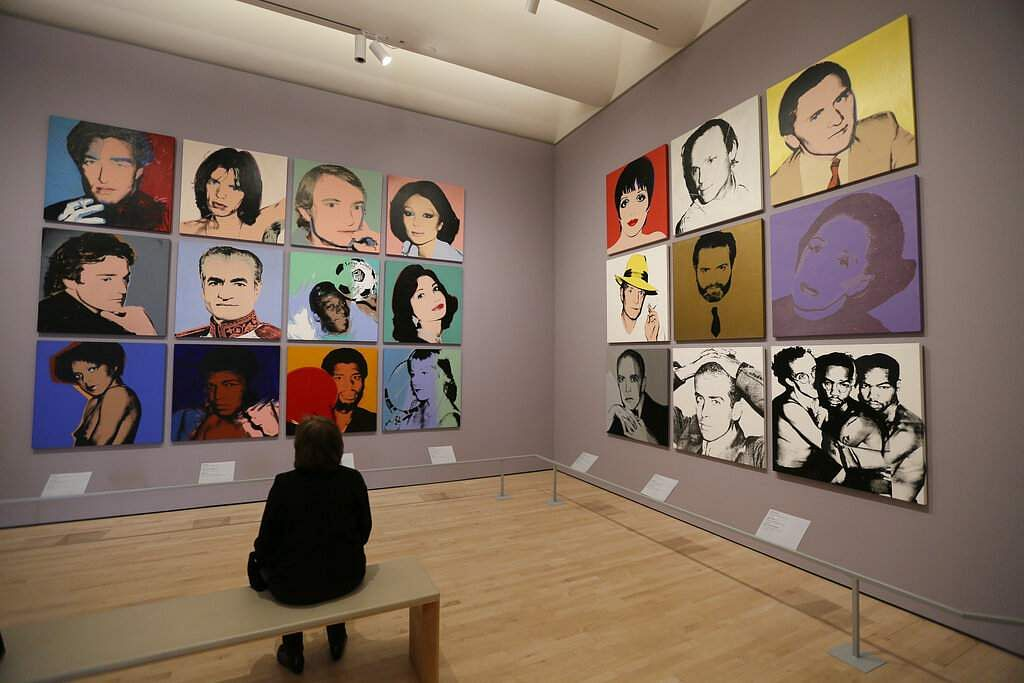 A woman views commissioned portraits from 1968-1987 at the exhibition, 'Andy Warhol _ From A to B and Back Again' in San Francisco. (AP Photo/Eric Risberg)