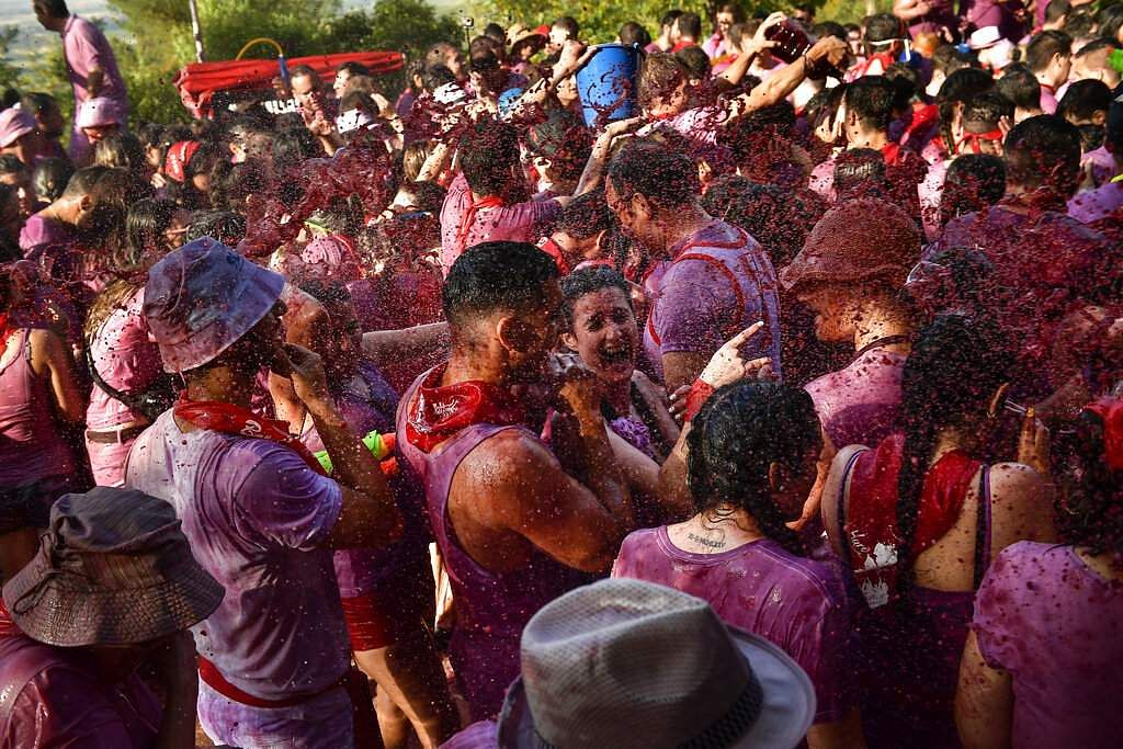 A reveler is covered in wine as people take part in this summer battle, throwing thousands of litres of red wine over each other, in the village of Haro, northern Spain. (AP Photo/Alvaro Barrientos)