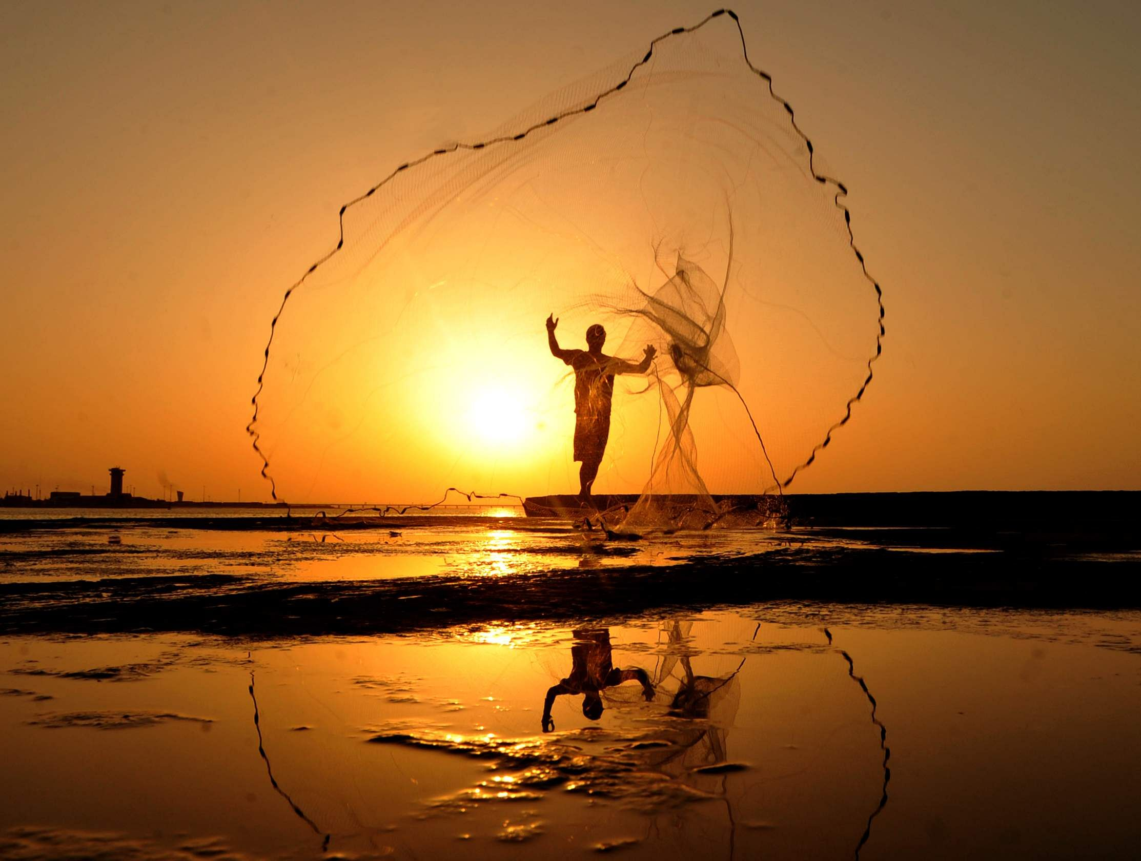 KUWAIT CITY, July 8, 2019 (Xinhua) -- Photo taken on July 7, 2019 shows a man casting a net for fishing in the sunset in Kuwait City, Kuwait. (Xinhua/Asad/IANS)