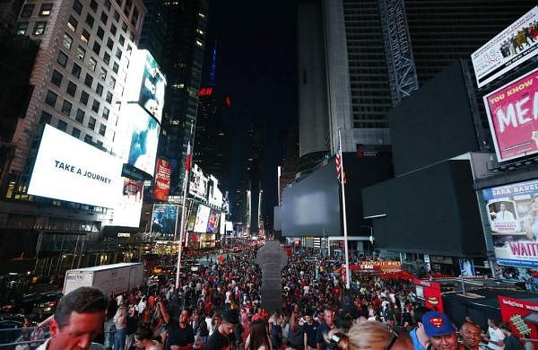Times Square's towering electronic screens and marquees were blacked out during a power outage in Manhattan, New York leaving many businesses in the theatre district crippled. (AP Photo/Michael Owens)