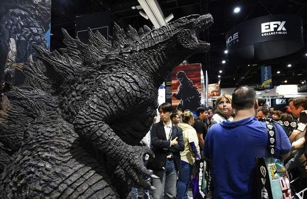 Marielle Larson, 3, looks over her father Derek's shoulder at an oversized Godzilla model at the 2019 Comic-Con International: San Diego. (Photo by Chris Pizzello/Invision/AP)