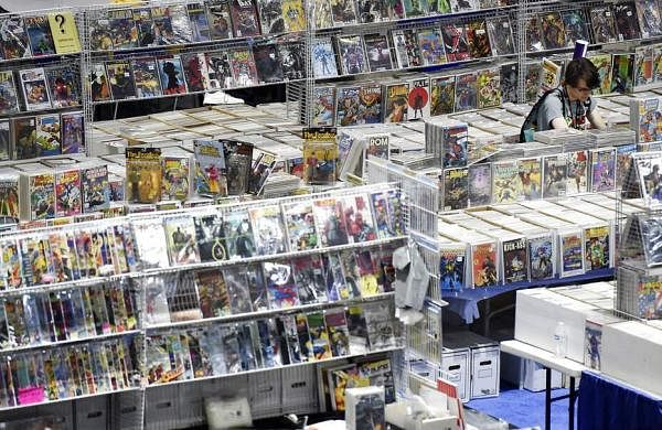 A lone Comic-Con attendee searches through stacks of comic books on the convention floor during Preview Night at the 2019 Comic-Con International: San Diego. (Photo by Chris Pizzello/Invision/AP)